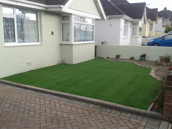 yard with fake grass and block paving