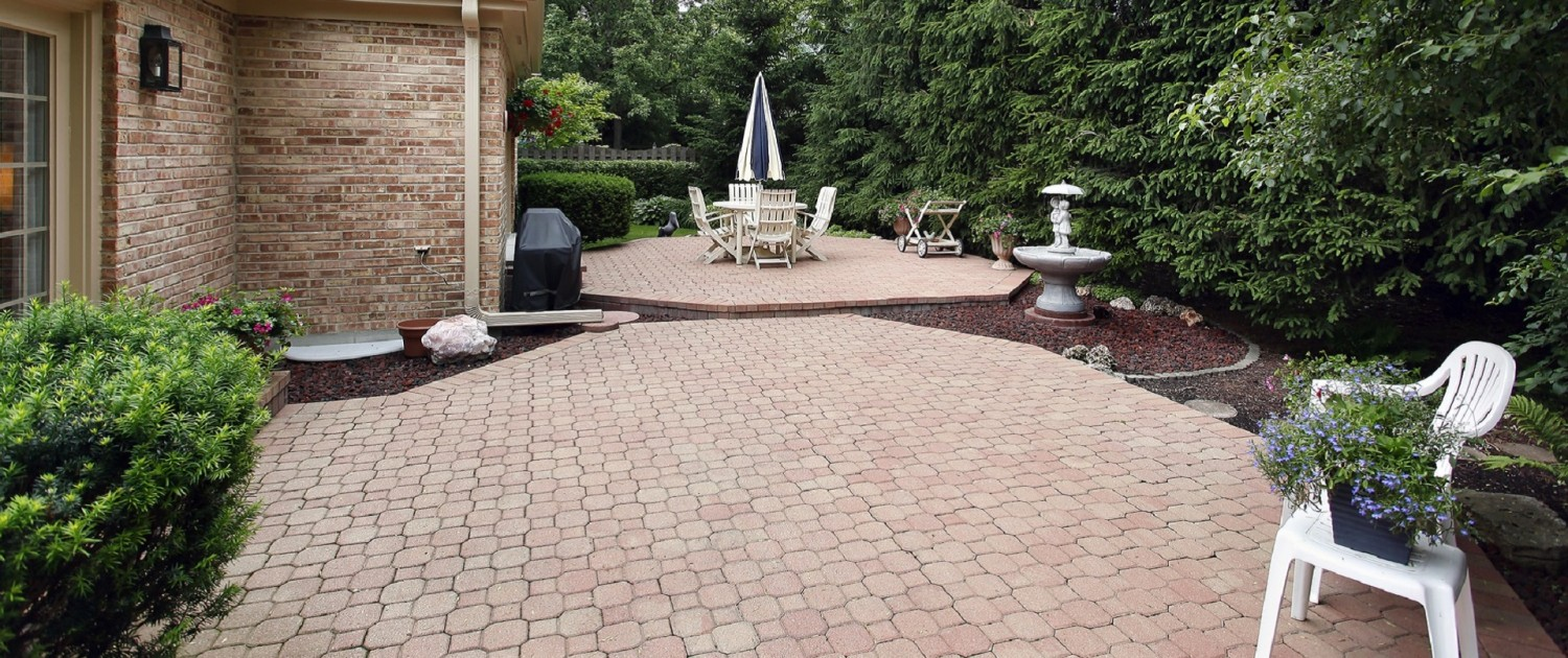 Brick patio with rock garden and white fountain